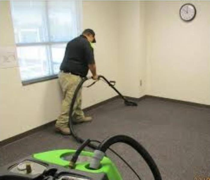 man cleaning carpet with wand and hose