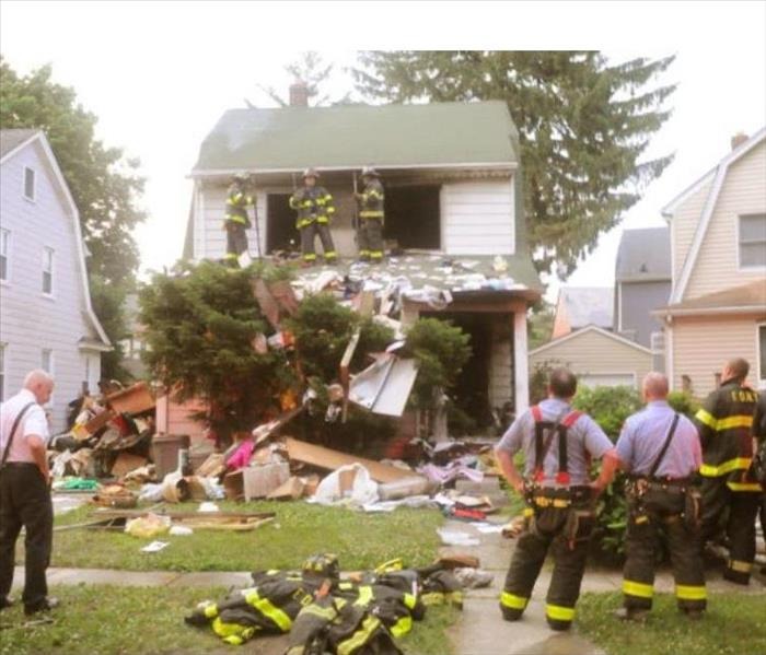 two story house with debris on ground and 6 firefighters